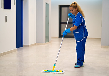 A cleaning lady mops the floor in an office building