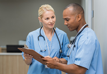 Medical multiethnic staff having discussion in a hospital hallway. Male and female nurse wearing blue scrubs working in a medical clinic. Two hospital workers discussing on laboratory test.