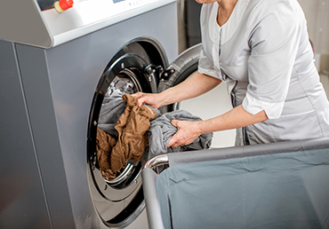 Senior washwoman taking of cleaned up towels from the washing machine in the laundry